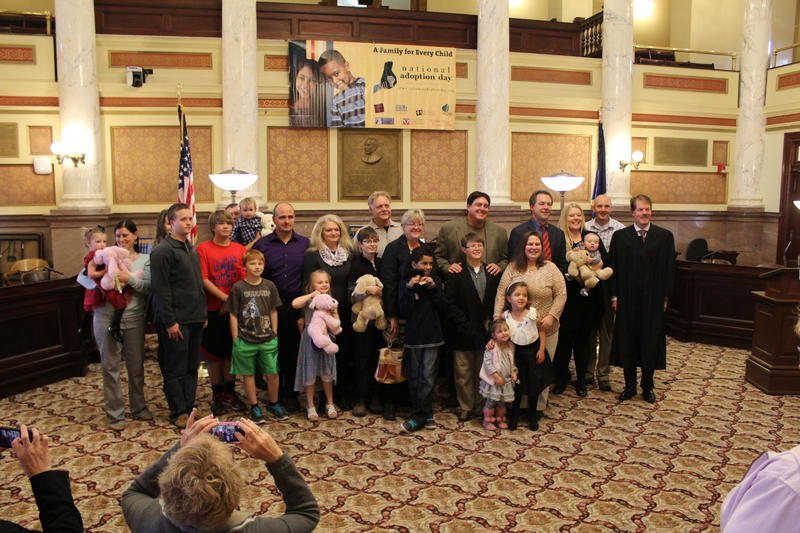 Five Helena-area families pose with their newly adopted children, and Gov. Steve Bullock.