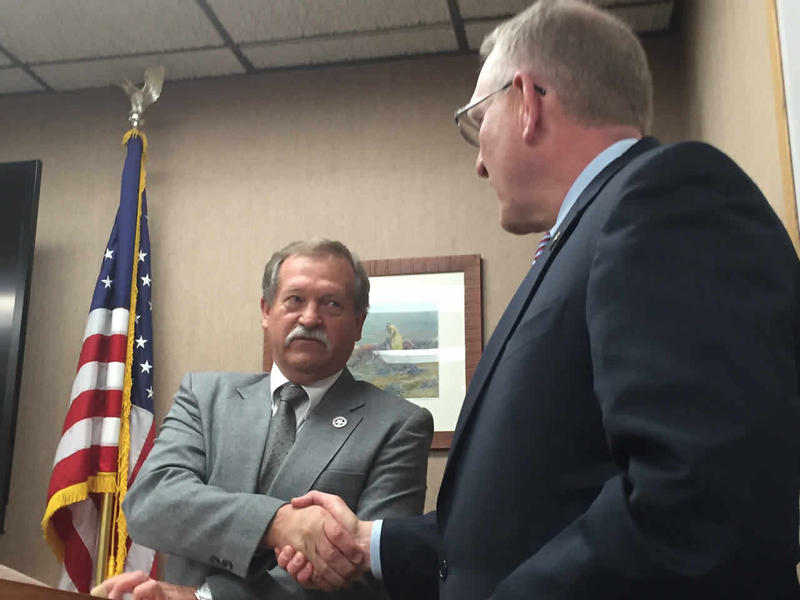 """New State Fire Marshal Stephen """"Dick"""" Swingley, shakes hands with Attorney General Tim Fox."""