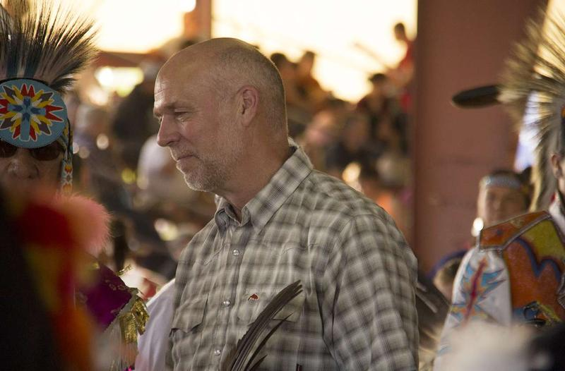 Greg Gianforte standing among dancers during the Arlee powwow grand entry.