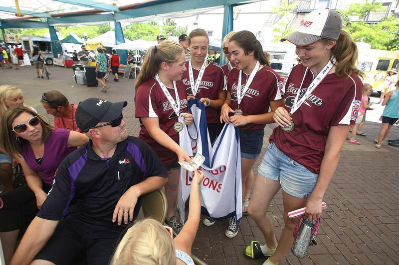 The Zootown All-Stars softball team from Missoula fundraises in Caras Park during Out to Lunch Wednesday, July 27 for their trip to Delaware and the softball Little League World Series.