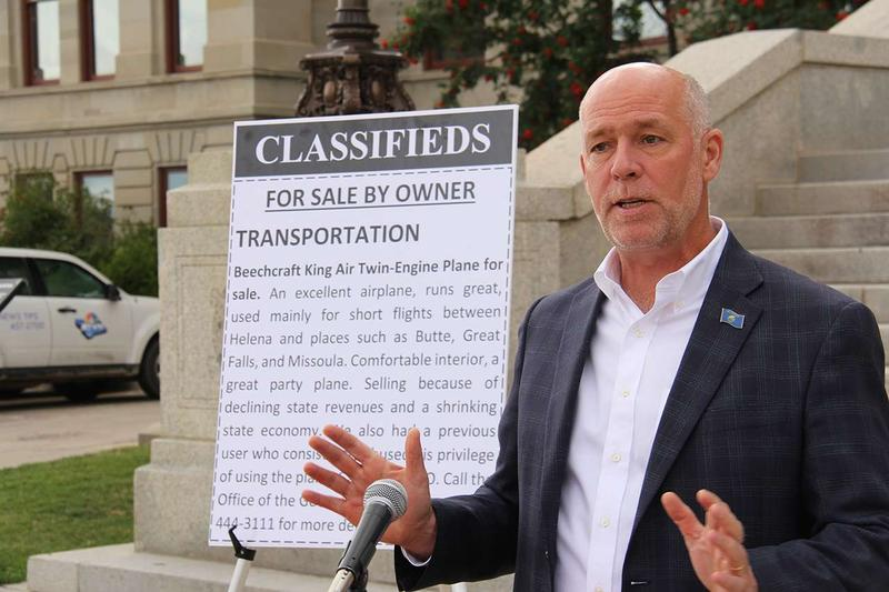 "Republican gubernatorial candidate Greg Gianforte stands in front of a poster-sized ""classified ad"" for the Montana state airplane. Gianforte says he'll sell the state plane if elected."