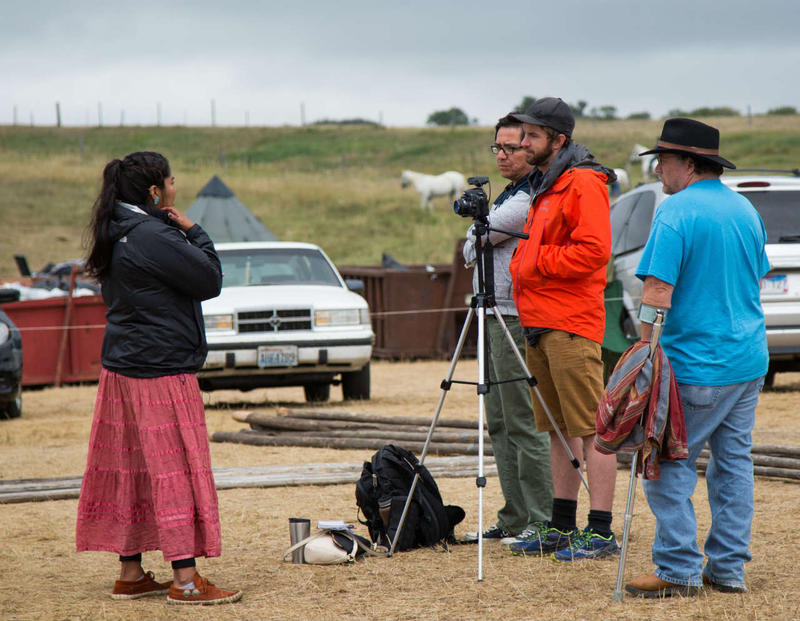 An onlooker watches as Matt Roberts and Jason Begay, center, interview Syracuse journalism student Jourdan Bennett-Begaye, about her eyewitness account of the clash between protestors and Dakota Access Pipeline security  on Saturday, Sept. 3, 2016.