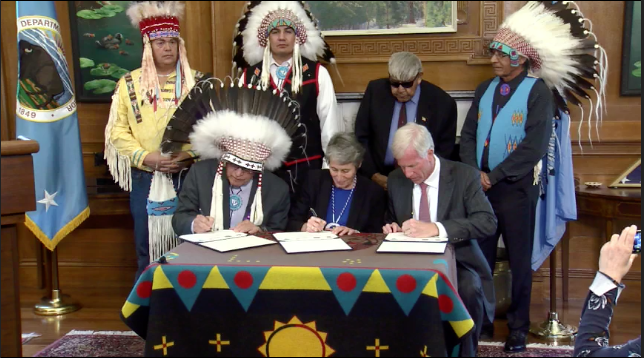 Blackfeet Tribal Chairman Harry Barnes, U.S. Interior Secretary Sally Jewell, and Devon Energy CEO David Hager sign a ceremonial document at the Department of Interior Headquarters in Washington DC, Wednesday morning, as Blackfeet leadership stand behind