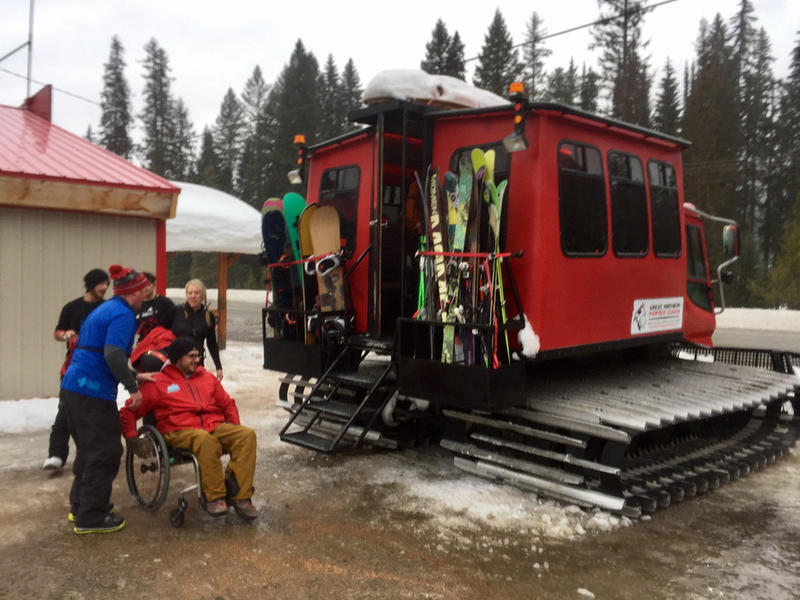 Lucas Grossi helps Odi Pierce into the cat at Great Northern Powder Guides in Olney. Pierce is one of seven extreme adaptive athletes participating in DREAM Adaptive's backcountry powder camp this year.