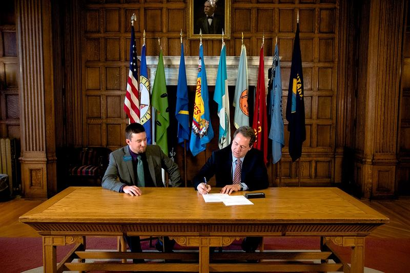 Rep. Casey Knudsen, R-Malta, left, looks on Friday as Gov. Steve Bullock signs a bill he carried that would define electric fences. This was Knudsen's first bill signed into law, and one of 12 the governor signed this week.