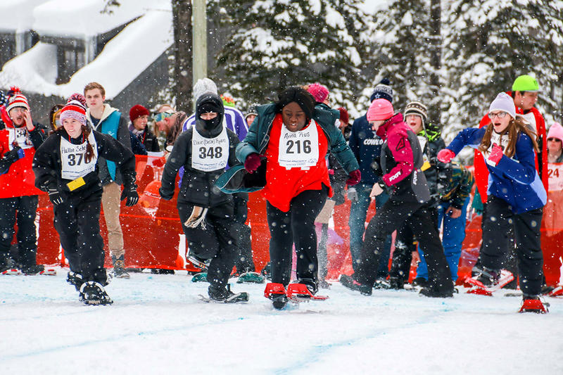 Racers sprint out the gate at the start of the women's snowshoe race.
