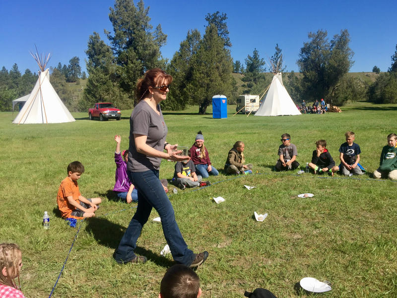 Georgia Smies, an aquatic biologist for the Flathead Tribes, plays a game about the impacts of aquatic invasive species with students from Lolo