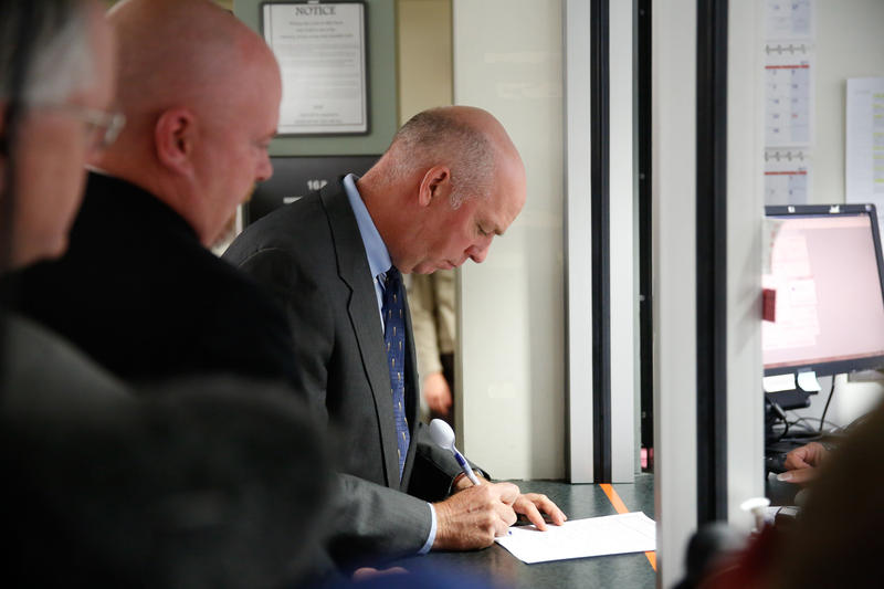 Gianforte signs paperwork after his sentencing at the Gallatin County Justice Court.