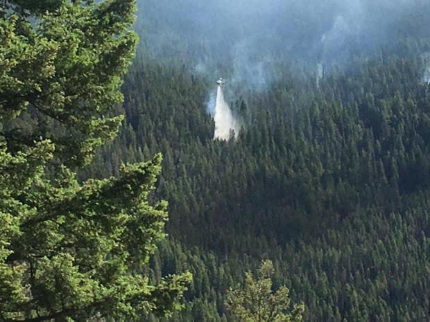 A helicopter drops water on the Slide Rock Fire on July 14th