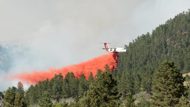 A heavy air tanker drops retardant on the July fire on Monday