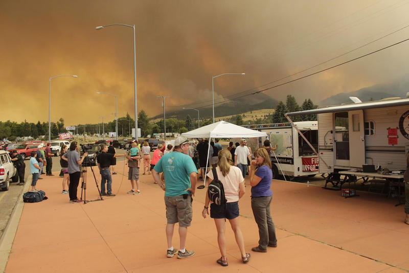 Lolo area residents gather at an incident command site Friday, August 18 as evening winds stoke the Lolo Peak Fire.
