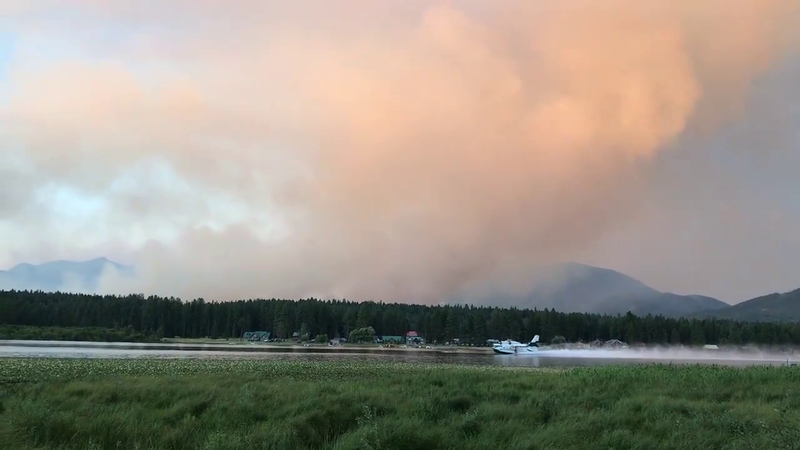 A super scooper plane loads up at Seeley Lake on the evening of August 1, while fighting the Rice Ridge Fire visible in the background.