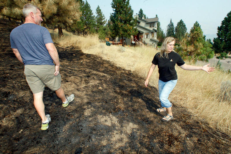 Dan and Michelle Schurg show how close the Lolo Peak Fire got to their home in the Folsom Road neighborhood near Florence.