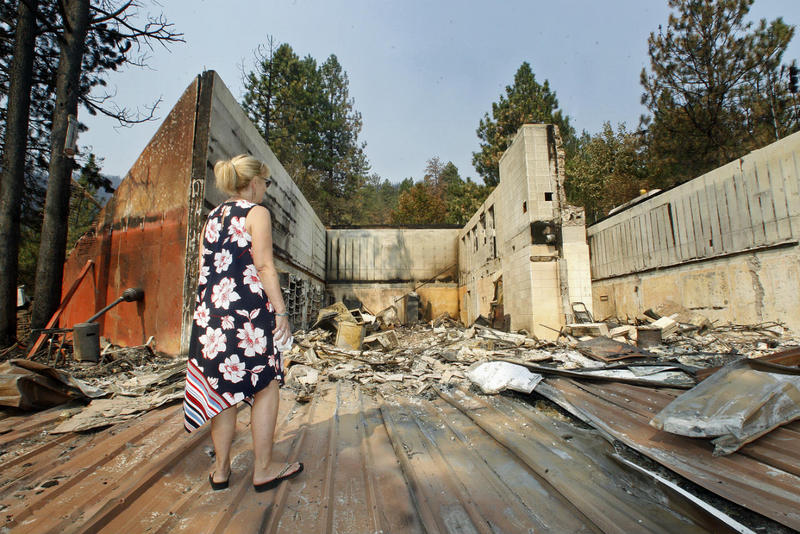 Jackie Stermitz looks over the remains of her Florence area home, which burned in the Lolo Peak Fire on August 17, 2017.