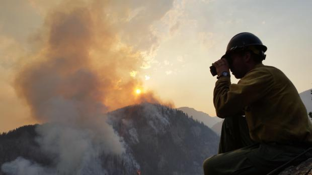 West Fork firefighter serving as a lookout for Hotshot crews working below on the Nelson Creek fire.