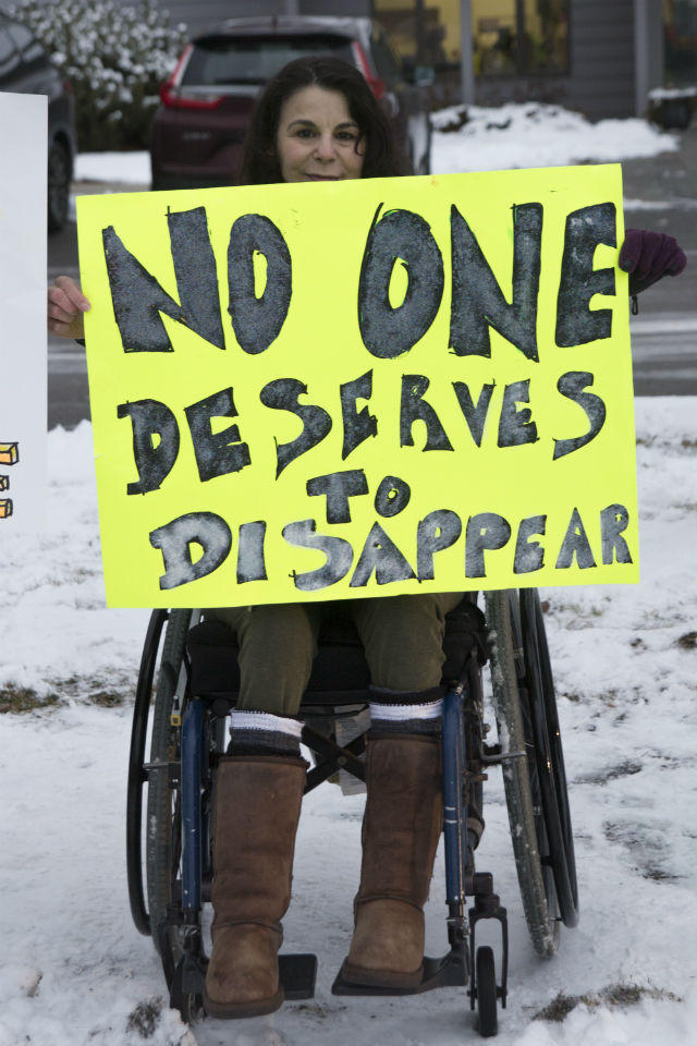 An woman holds a sign during the picket of Western Montana Mental Health Center in Missoula, Dec. 18, 2017.