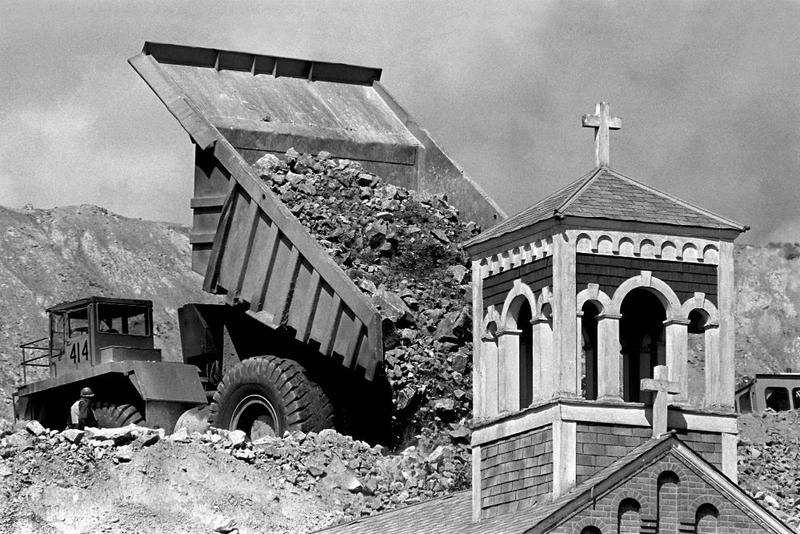 A mining dump truck buries the abandoned Holy Saviour Church in the McQueen neighborhood in Butte during the expansion of the Berkeley Pit.