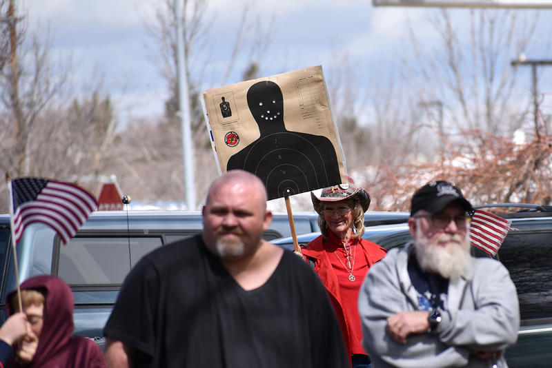 Tish Haas (background) waves a shooting target with a bullet hole smiley face at a gun rally in Kalispell April 15, 2018.