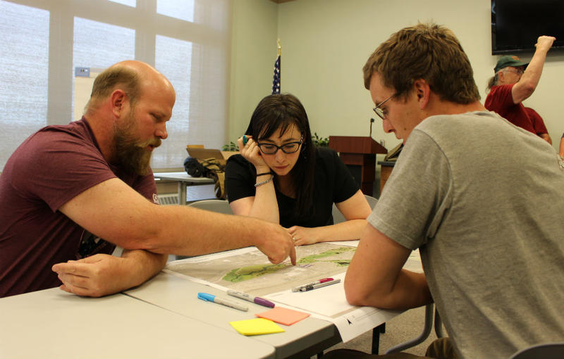 Dave Hutchins (L) and Daniel Hogan look over plans for the cleanup and restoration of the SIlver Bow Creek corridor with Julia Crain, a special projects planner with Butte-Silver Bow county