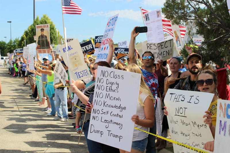 Protesters hold signs outside the Great Falls area where President Trump is campaigning, July 5, 2018.