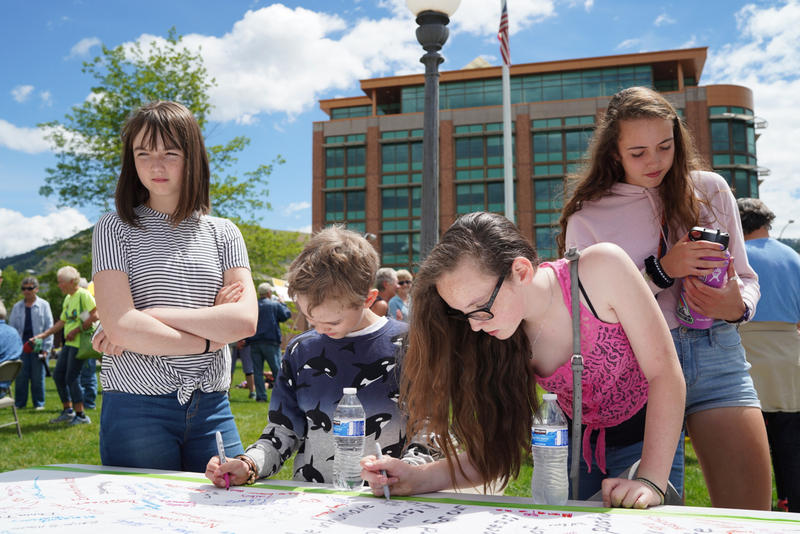 "From left, Cate, Robbie, Claire and Maggie Gibbons sign a banner protesting ""the inhumane treatment of asylum seekers,"" addressed to Sen. Steve Daines at a protest outside of the Missoula County Courthouse in Missoula, Mont. on Saturday, June 30, 2018"