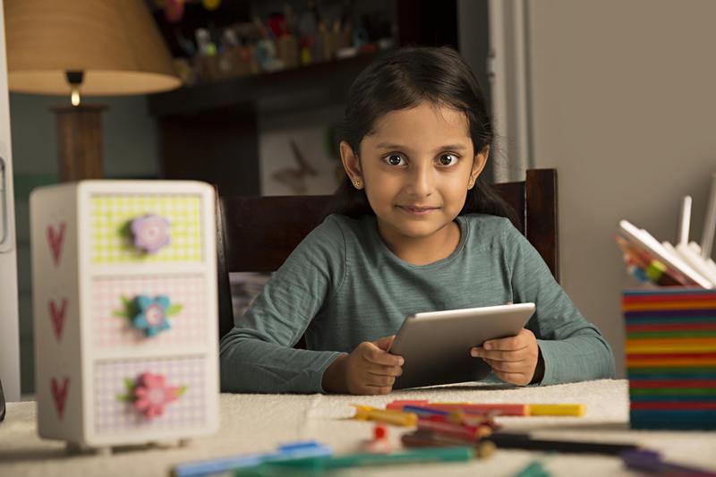 Girl doing homework using a tablet. Stock photo.