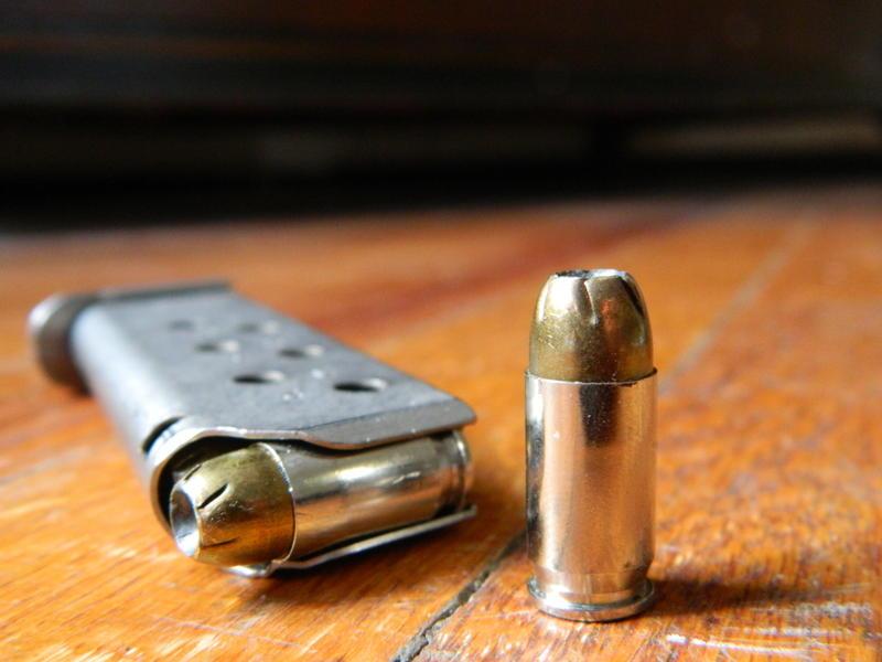 A handgun magazine and bullet.