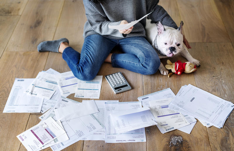 A woman a dog sit next to a pile of bills. Stock photo.