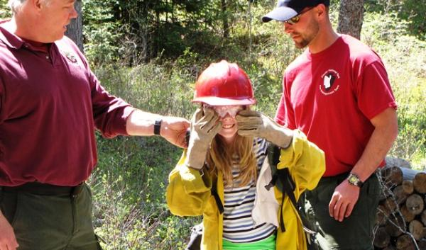 A student helps firefighters demonstrate the equipment they carry during the Flathead Forestry Expo.