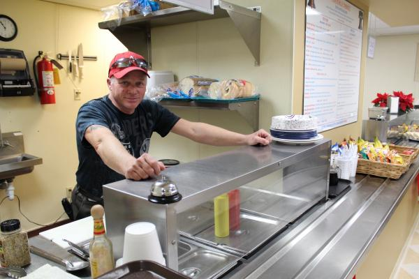 Politically Correct Cafe owner Larry Strang is back to work after a frozen pipe broke in the Capitol and flood waters closed his cafeteria for a week.