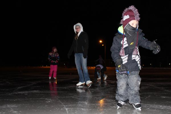 Cooper Larson (right) shuffles around the ice as instructor Megan Williams looks on.