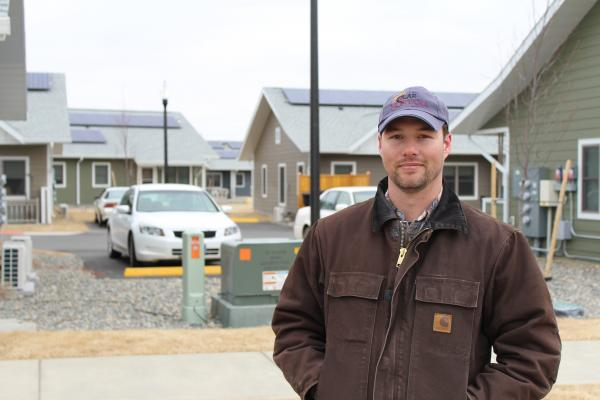 Solar Montana Owner Jackson Isbell stands in front of his installation at Helena's River Rock Residences.