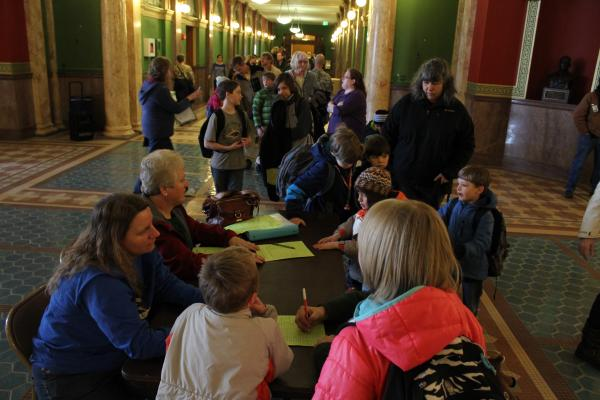 Jefferson Elementary students and their parents sign out with school officials Friday from the Capitol Rotunda, the school's evacuation area.