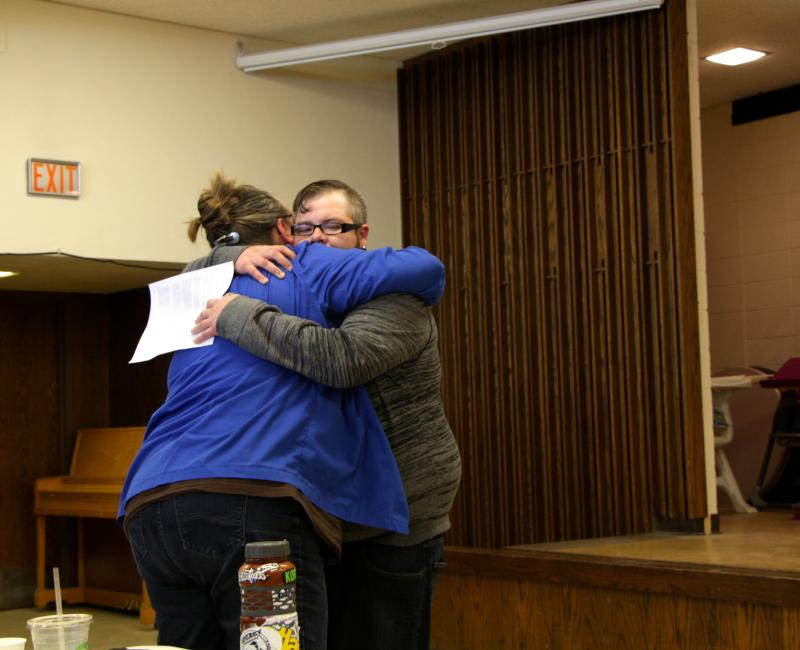 Opening speaker Jameson Danielson hugging his boss from work after he shared his homeless experience with participants