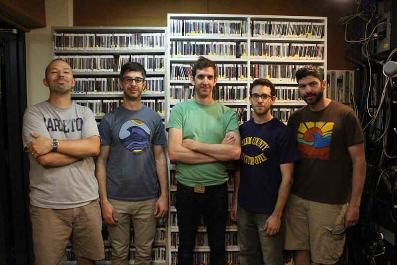 Five men in t-shirts standing in front of a wall of CDs.