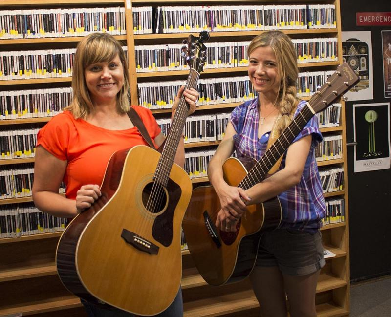 Two women in the KUMD studio holding guitars and smiling for the camera