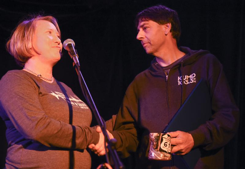 Maija Jenson and John Bushey shaking hands in front of microphone, John is holding a mug