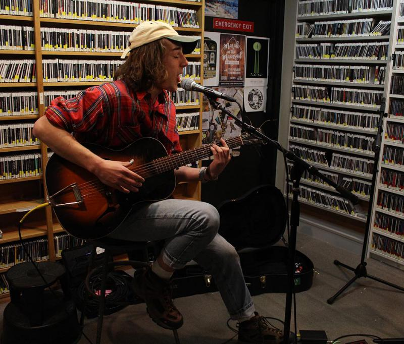 Young man sitting on a stool playing guitar and singing in a radio studio