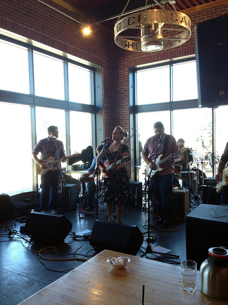 Band performing in front of sunny windows
