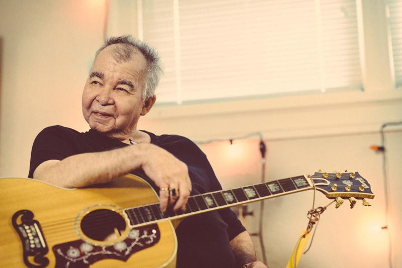 John Prine playing guitar