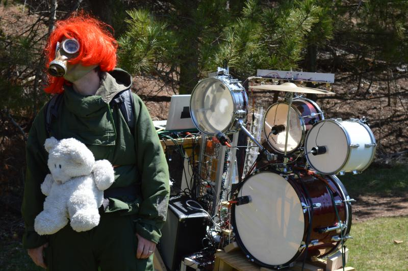 Man in red wig and gas mask with a white teddy bear strapped in front of his body and a cart of drums