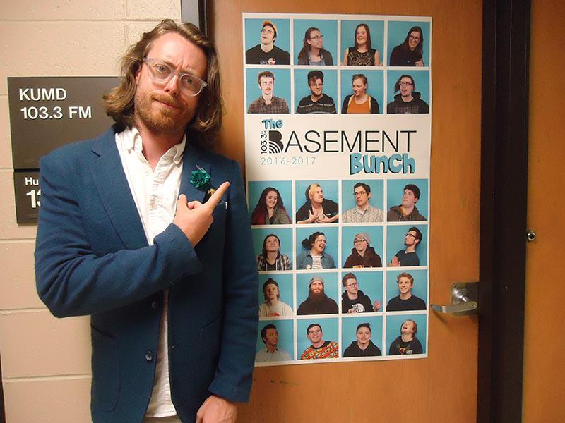 Man in a white shirt and blue jacket with long hair and glasses pointing to a poster on the door of KUMD.