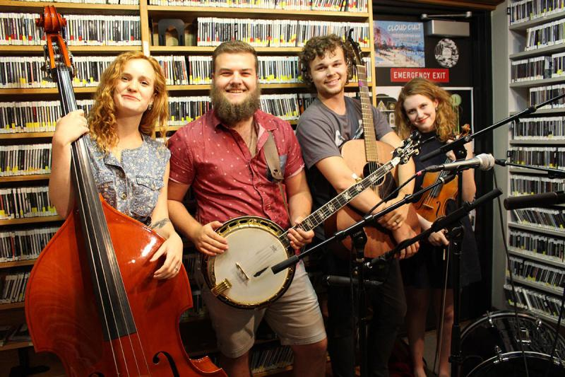 Female stand up bass player, male banjo player, male guitarist, and female fiddle player standing in front of a wall of CDs