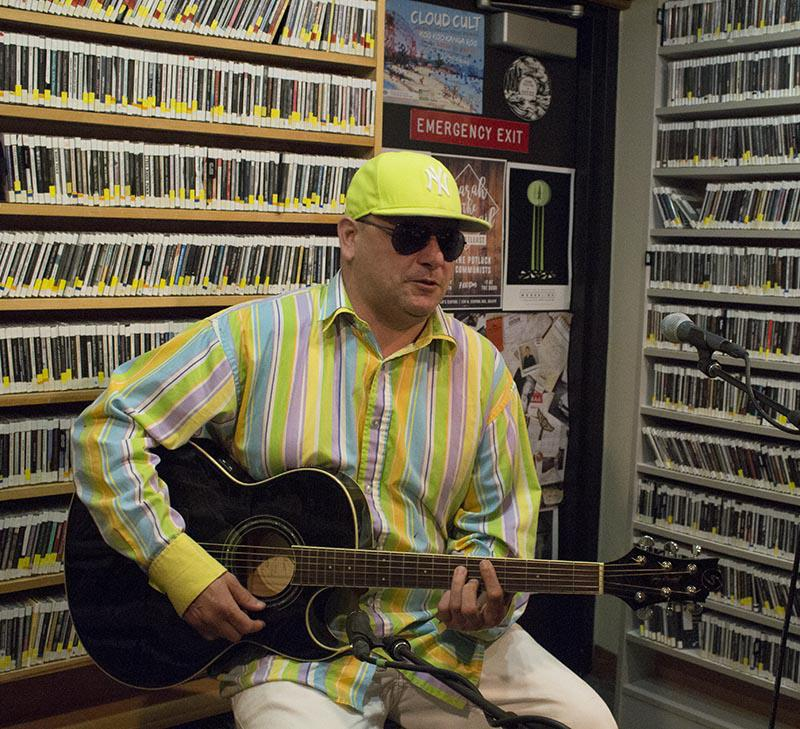 Man in bright yellow hat, brightly striped shirt, and sunglasses sitting on a stool playing guitar