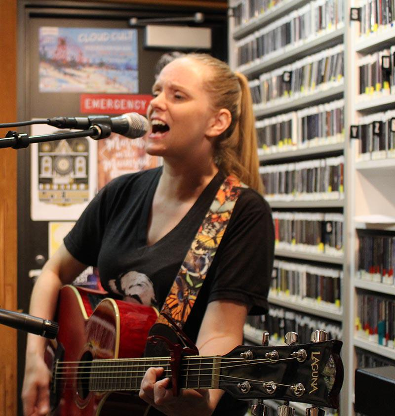 Woman playing guitar and singing in front of shelves of CD