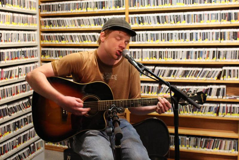 Man playing a guitar and singing into a microphone