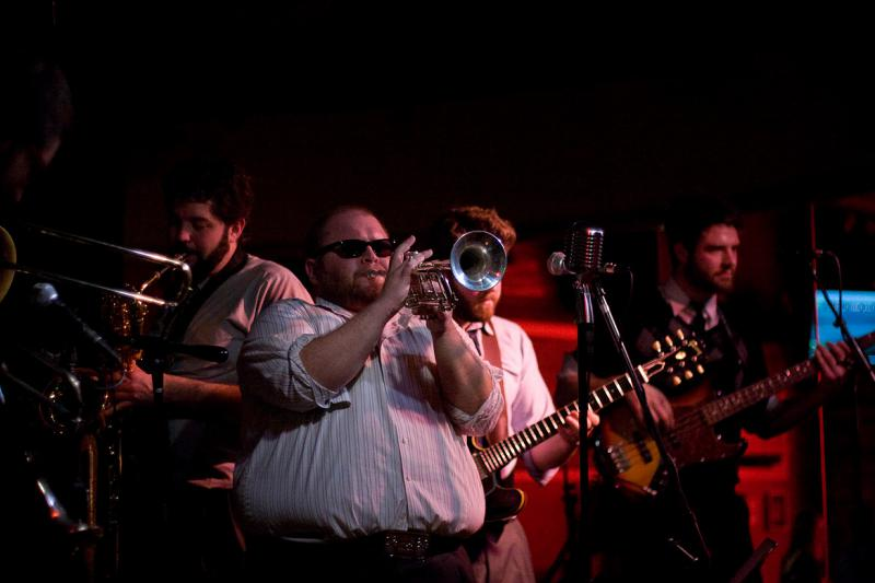 Man wearing sunglasses and playing a trumpet in front of a guitar player