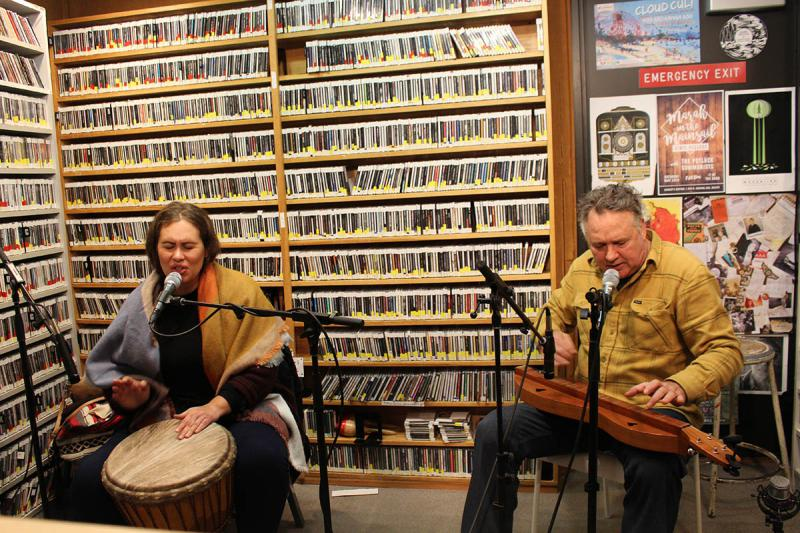 Woman playing a djembe and singing into a microphone, man playing a dulcimer and singing into a microphone