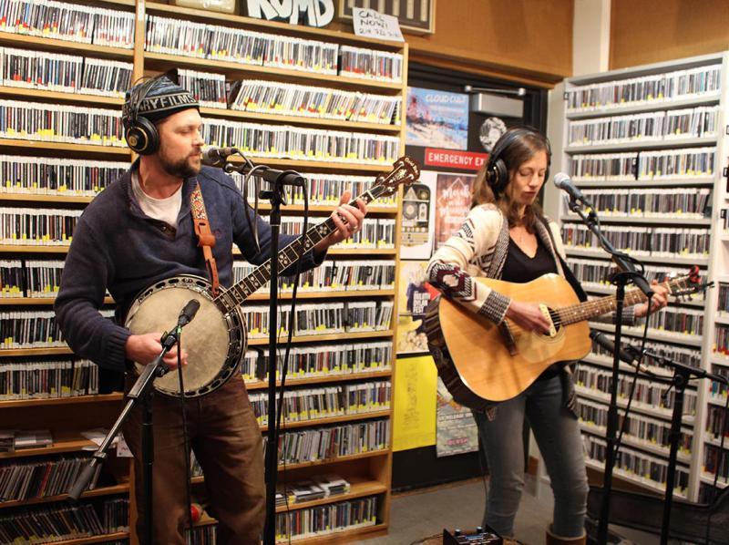 Man playing banjo and a woman playing guitar