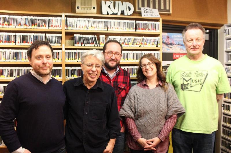 Four men and one woman standing in front of shelves of CDs